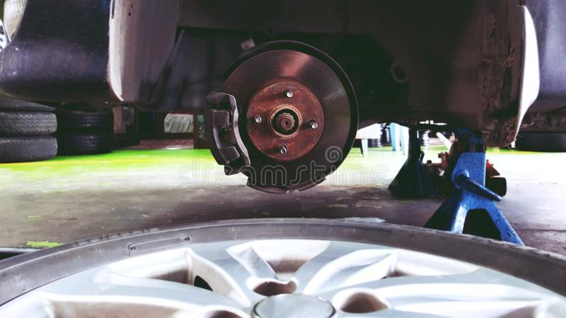 关闭车,在新的轮胎替换的过程中汽车修理工的闸圆盘修理的 免版税库存图片