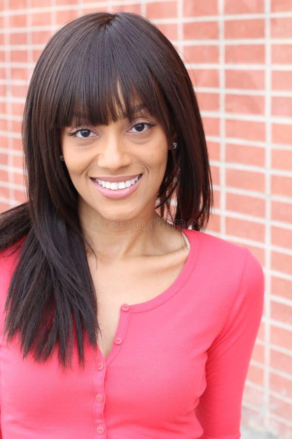 关闭软软地微笑一个年轻和可爱的非裔美国人的黑人妇女的秀丽的画象有完善的皮肤的, 免版税图库摄影