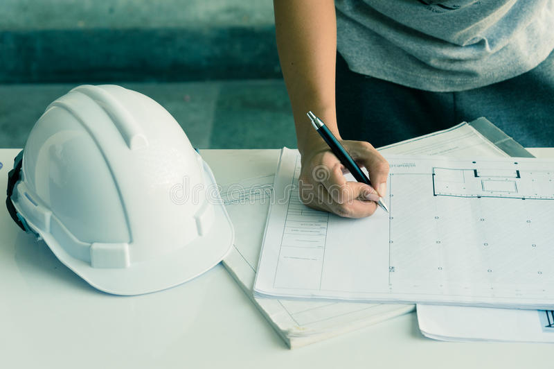 关闭运转在桌,他图画项目剪影在建造场所或办公室上的工程师手 库存图片