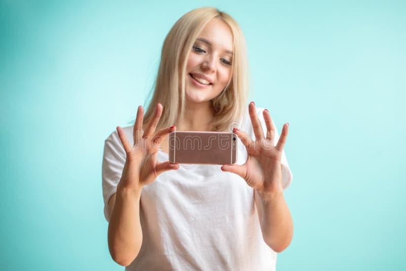 关闭迷住白肤金发的制造的selfie画象由她的智能手机 免版税库存照片