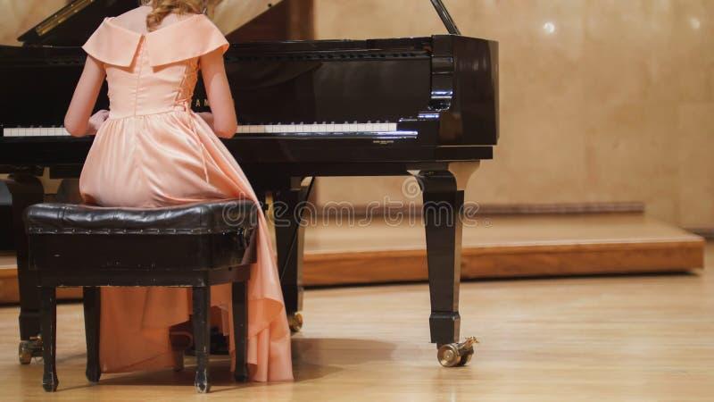 关闭逗人喜爱的少年女孩戏剧钢琴看法在音乐厅里在场面 库存照片