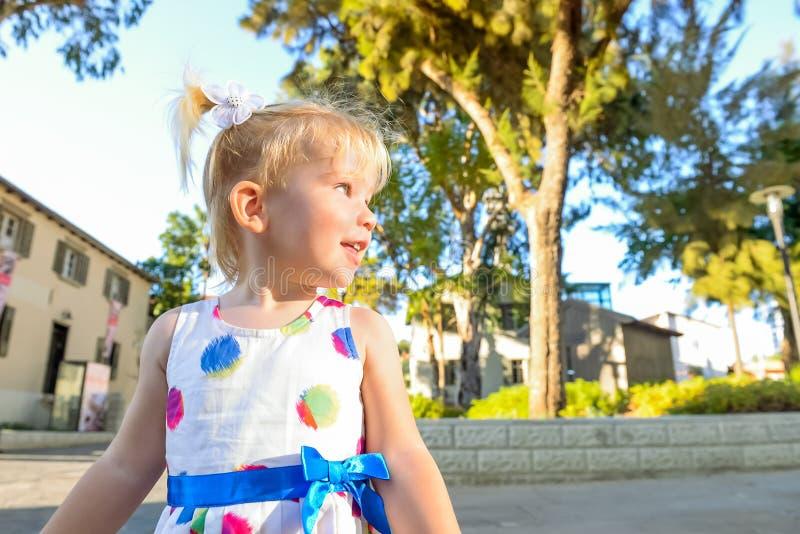 关闭逗人喜爱的矮小的blondy小孩女孩画象看在旁边在有大厦和树的城市公园的礼服的在backg 库存照片