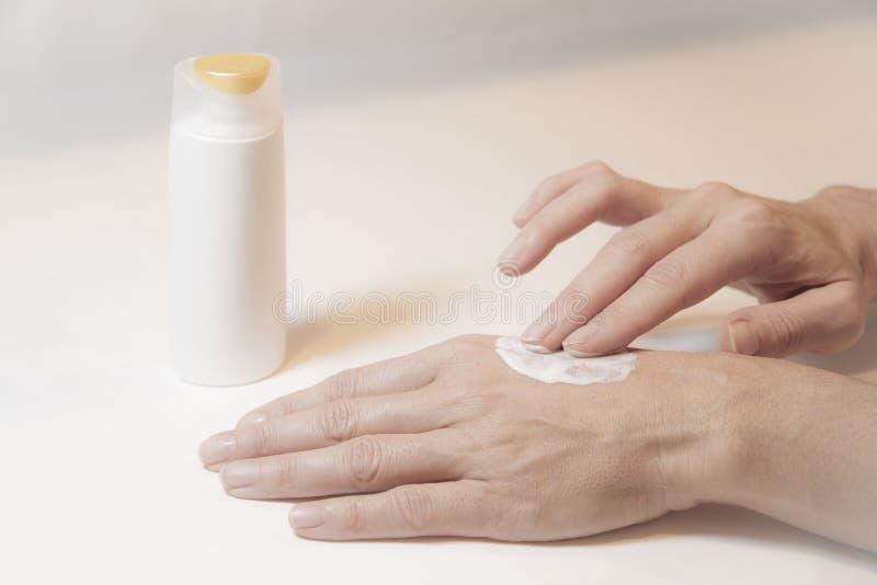 关闭通过摩擦奶油照顾她自己用两个手指在她的左手背面妇女的手 免版税库存图片