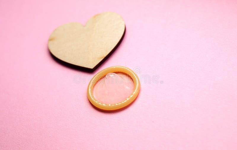 关闭避孕套和木心脏在桃红色背景 E 免版税库存照片