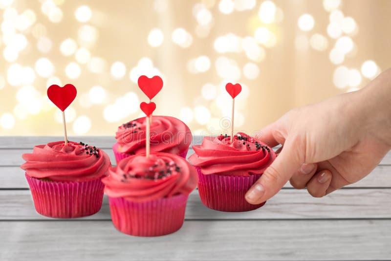 关闭采取杯形蛋糕用心脏棍子的手 图库摄影