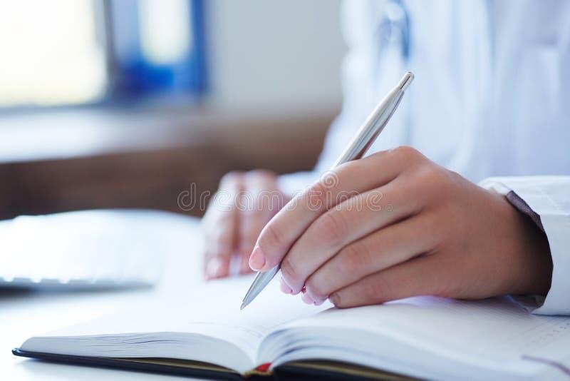关闭采取笔记的女性医生` s手 保护回合、耐心参观检查、医疗演算和统计 免版税库存图片