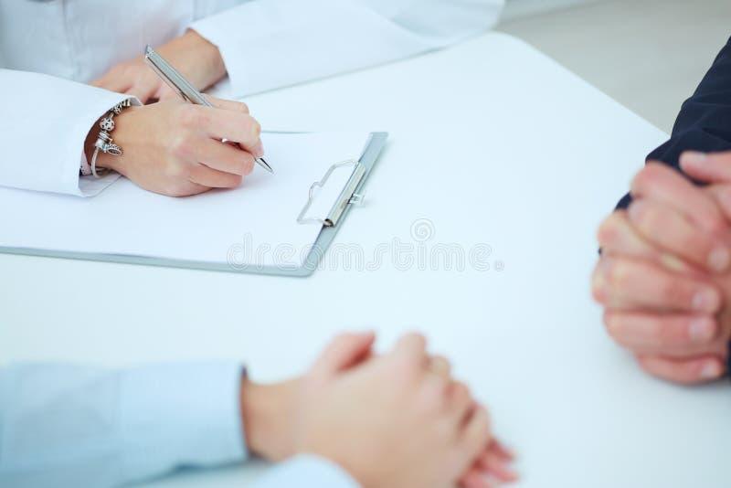 关闭采取笔记的患者手和医生 保护回合、耐心参观检查、医疗演算和统计 免版税图库摄影