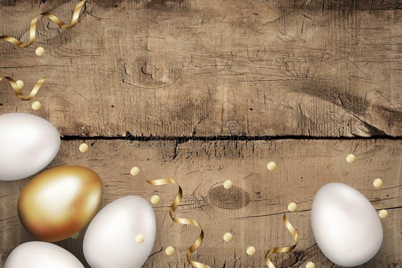 关闭金子和白色复活节彩蛋在木背景 土气背景的grunge 复活节彩蛋和金黄蜒蜒五彩纸屑 免版税库存照片