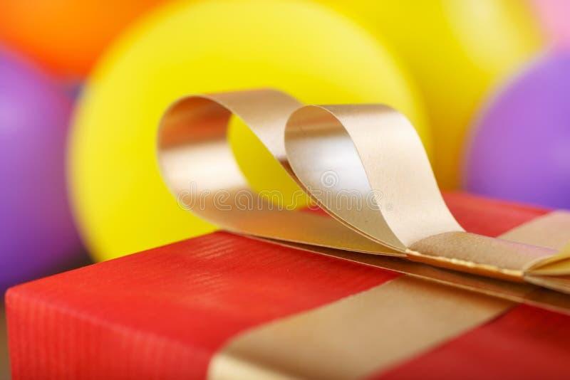 关闭金黄有金丝带的弓红色礼物盒 免版税库存照片