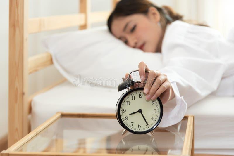 关闭闹钟的亚裔年轻秀丽妇女在早晨后,不用看时钟和懒惰对工作在假日 ?? 免版税库存图片