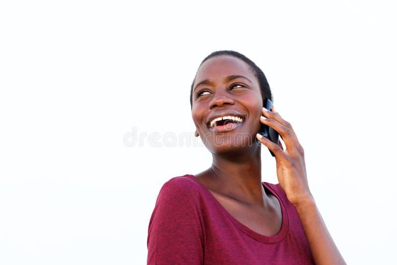 关闭非裔美国人的少妇谈话在手机被隔绝在白色背景 库存图片