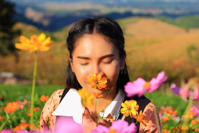 关闭面孔,白种人妇女和表示幸福,有黄色和桃红色comos花的俏丽的女孩 库存照片