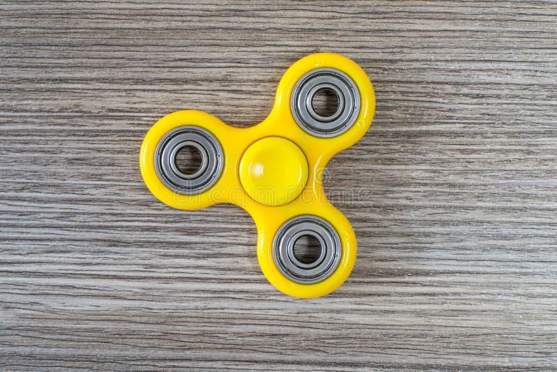 关闭顶面大角度在普遍的黄色坐立不安锭床工人上,反对灰色木背景iso的应力消除玩具看法照片  库存图片