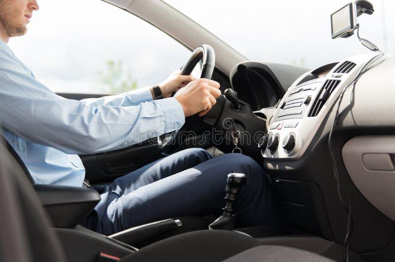 关闭驾驶汽车的衣服的年轻人 图库摄影