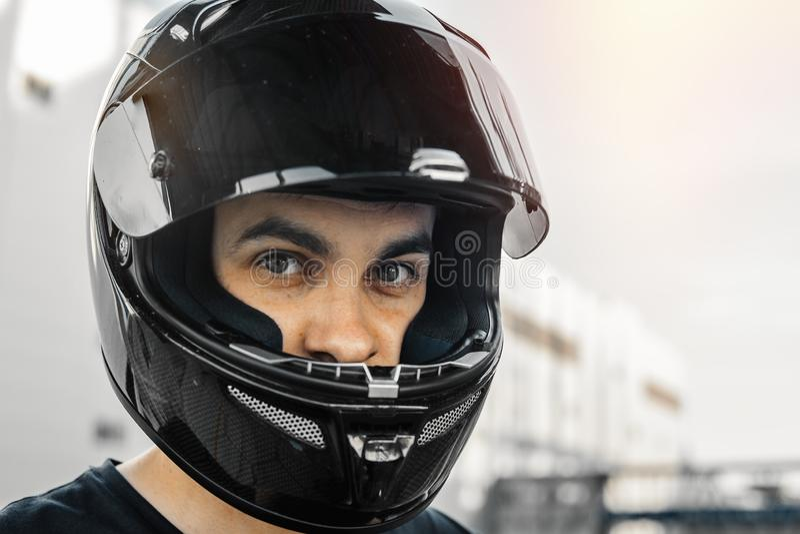 关闭骑自行车的人画象黑光滑的盔甲的在都市背景 免版税图库摄影