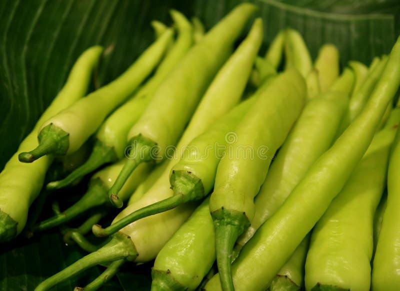 关闭鲜绿色的新鲜的辣椒的果实堆在香蕉叶子的 库存照片