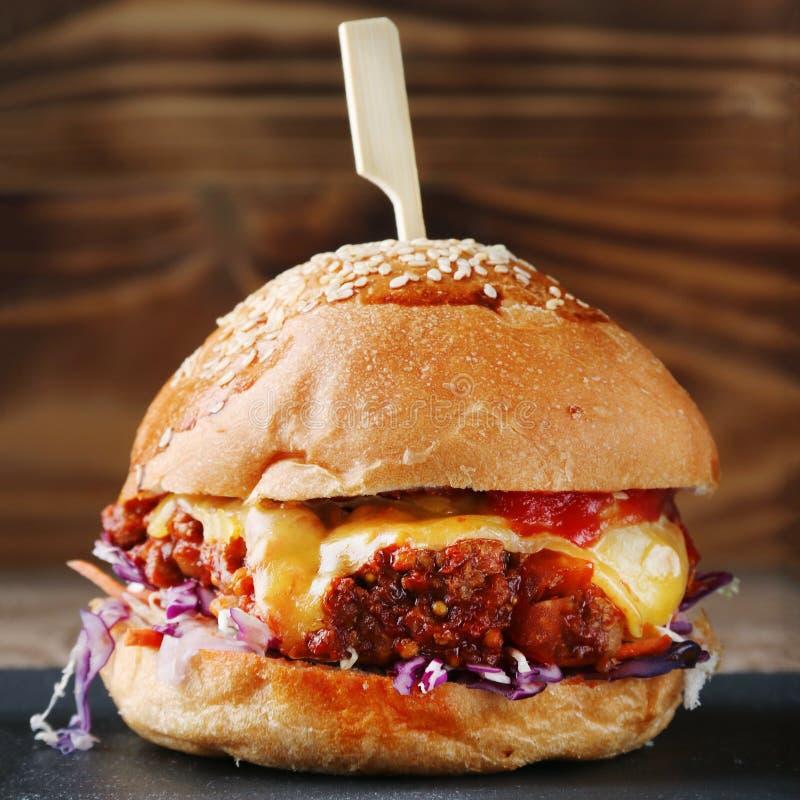 关闭鲜美汉堡用牛肉乳酪和菜 免版税库存照片