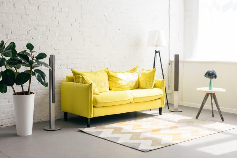 关闭黄色沙发、花绿色植物和花束看法在花瓶的在咖啡桌上 免版税库存图片