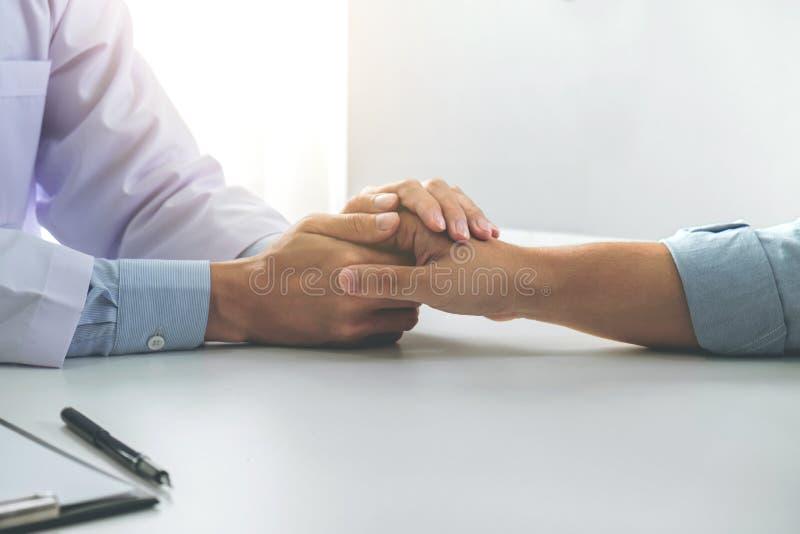 关闭鼓励的医生感人的耐心在医院,欢呼和支持患者,坏消息,我的手和同情 免版税库存图片