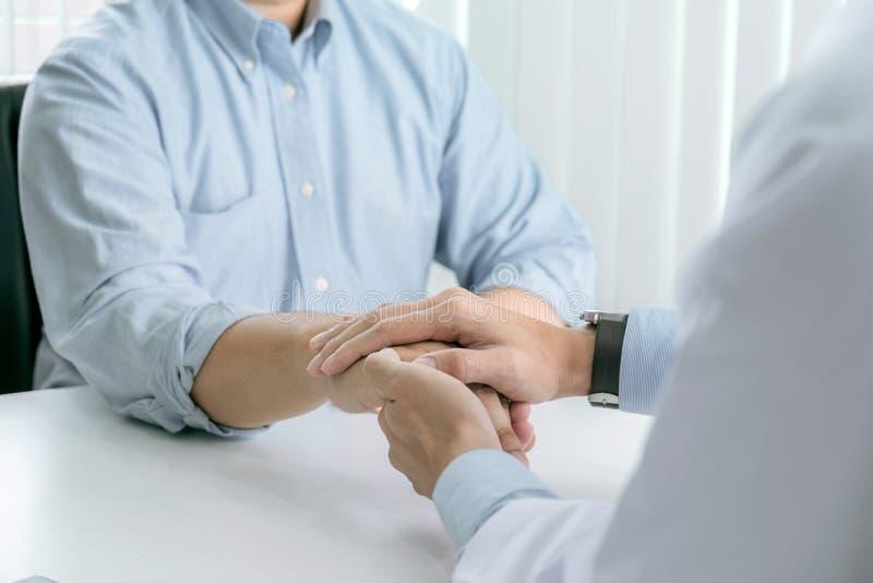 关闭鼓励的医生感人的耐心在医院,欢呼和支持患者,坏消息,我的手和同情 图库摄影