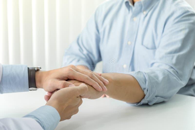 关闭鼓励的医生感人的耐心在医院,欢呼和支持患者,坏消息,我的手和同情 库存照片