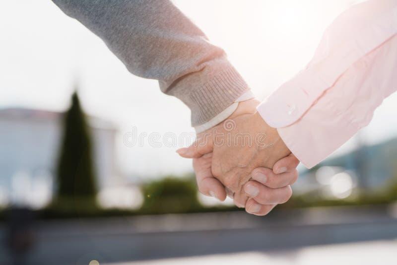 关闭 一对年长夫妇在握手附近走 他们沿一个美好的正方形走 免版税图库摄影