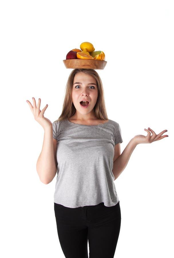 关闭年轻人惊奇的妇女哪些拿着一个木碗用果子:苹果,桔子,柠檬 维生素和健康吃 库存照片