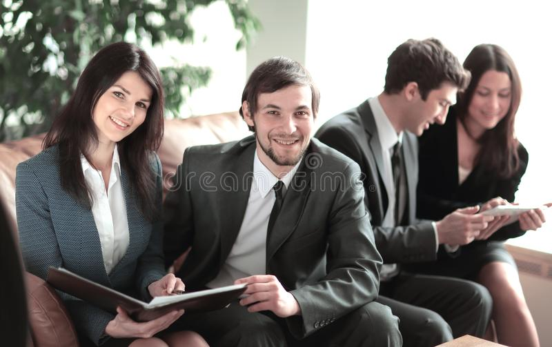 关闭 企业夫妇在办公室的大厅坐同事背景  免版税库存照片