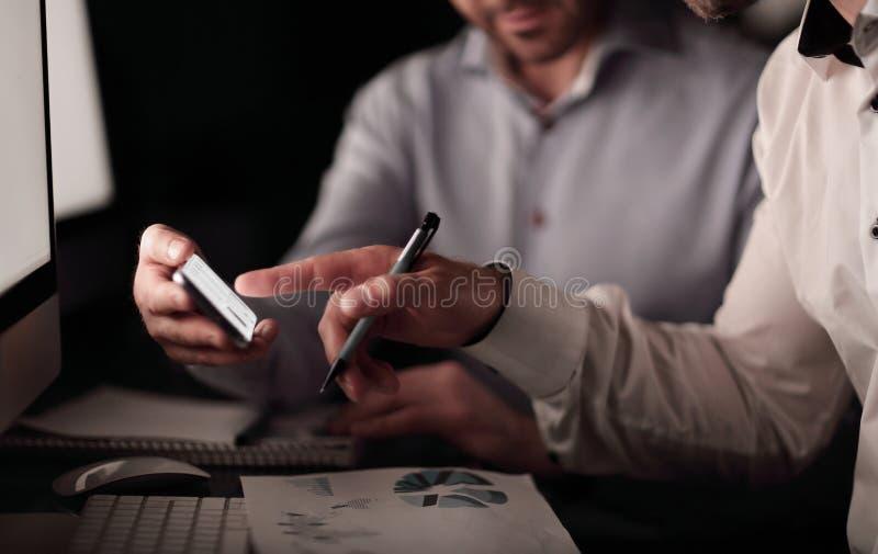 关闭 使用智能手机的商人检查财务数据 免版税库存图片