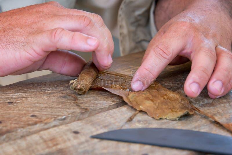 关闭滚动雪茄的手在古巴 免版税库存照片