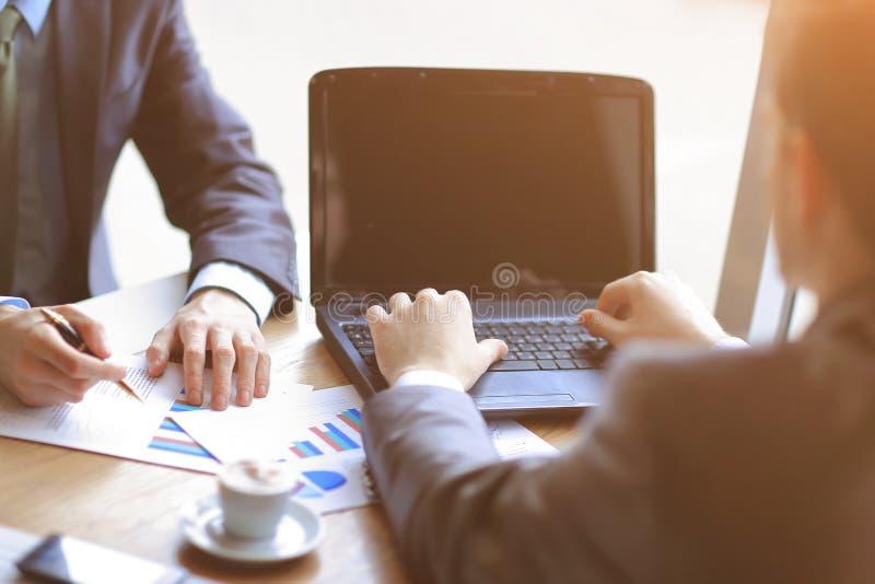 关闭 商人使用一台膝上型计算机检查财务数据 免版税图库摄影