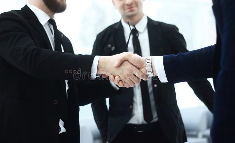 关闭 商务伙伴强的握手在办公室 免版税库存照片