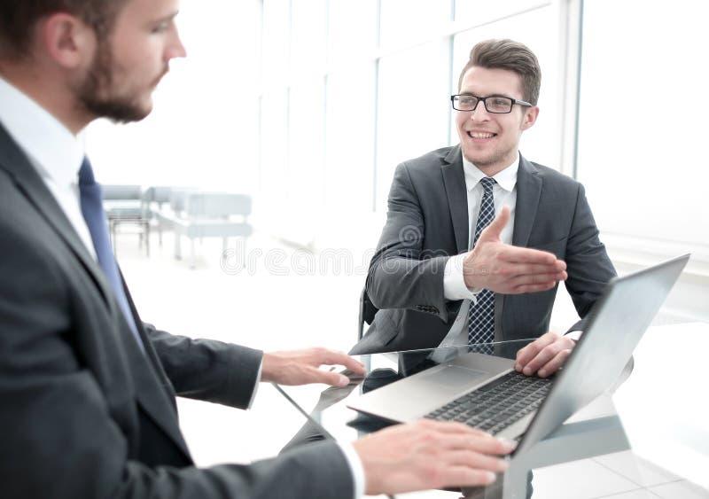 关闭 商务伙伴谈论坐在办公室桌上的信息 免版税库存图片