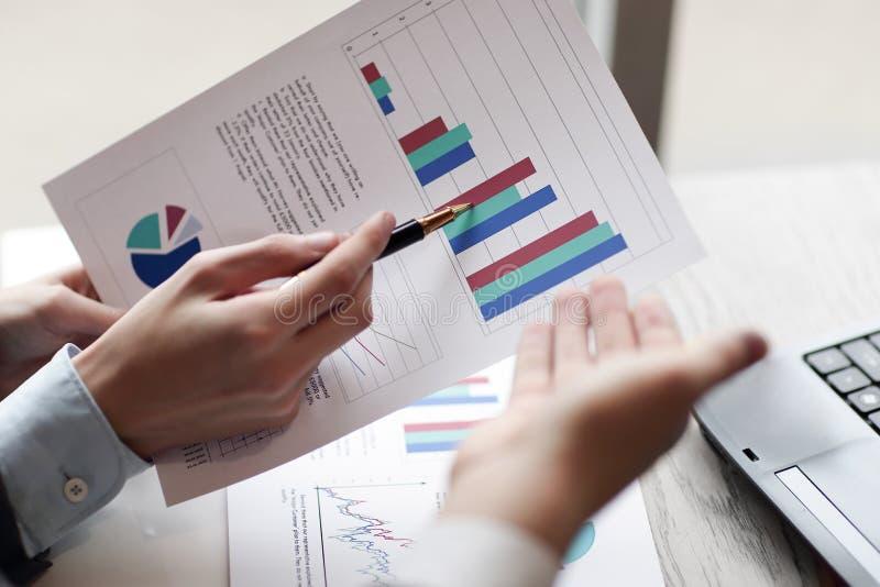 关闭 商务伙伴谈论财政业绩 到达天空的企业概念金黄回归键所有权 免版税库存照片