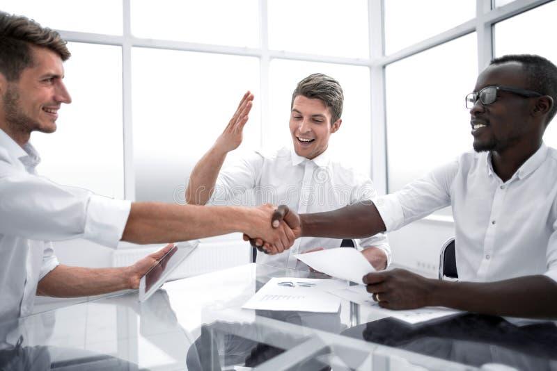 关闭 国际商务伙伴握手书桌的 免版税库存照片