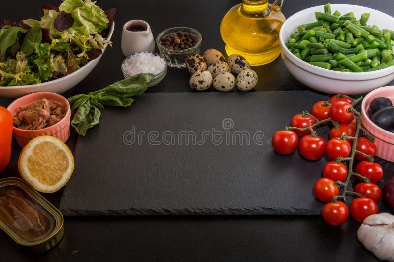 关闭 土气的生活仍然 做的法国传统niçoise nicoise沙拉成份 黑色背景 复制空间 库存照片