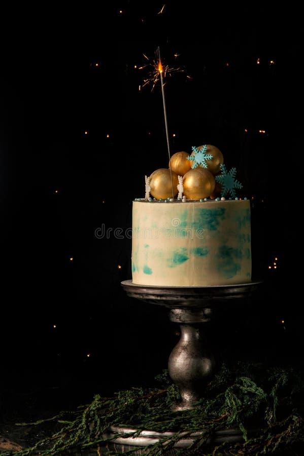 关闭 圣诞节蛋糕和一个燃烧的闪烁发光物欢乐地装饰它 与圣诞灯的黑暗的背景 库存照片