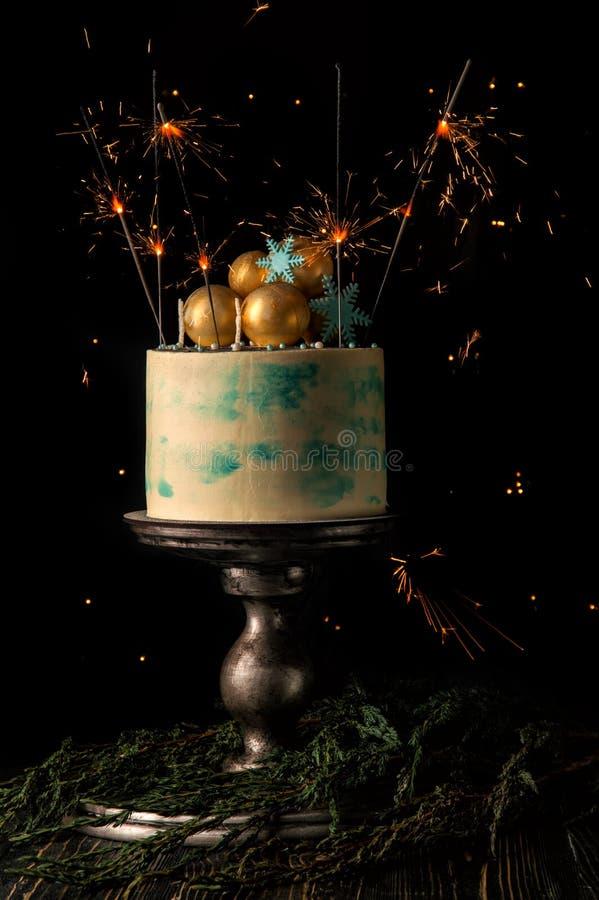 关闭 圣诞节蛋糕和灼烧的闪烁发光物欢乐地装饰它 与圣诞灯的黑暗的背景 免版税库存图片