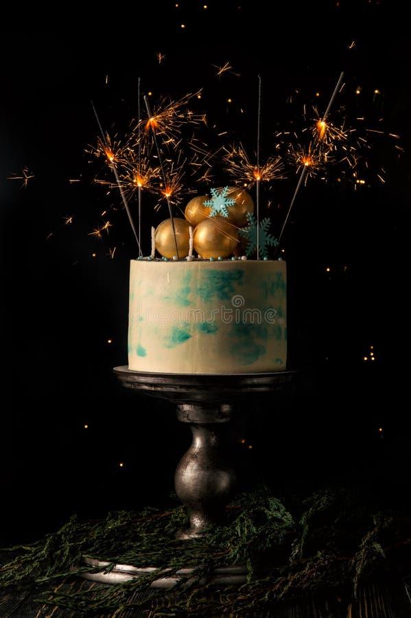 关闭 圣诞节蛋糕和许多灼烧的闪烁发光物欢乐地装饰它 与圣诞灯的黑暗的背景 图库摄影