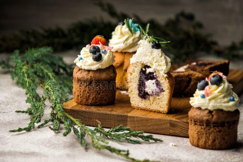 关闭 在裁减新近地烘烤了蓝莓淡紫色松饼,他们中的一个 用一个奶油色帽子装饰的上面用莓果 免版税库存照片