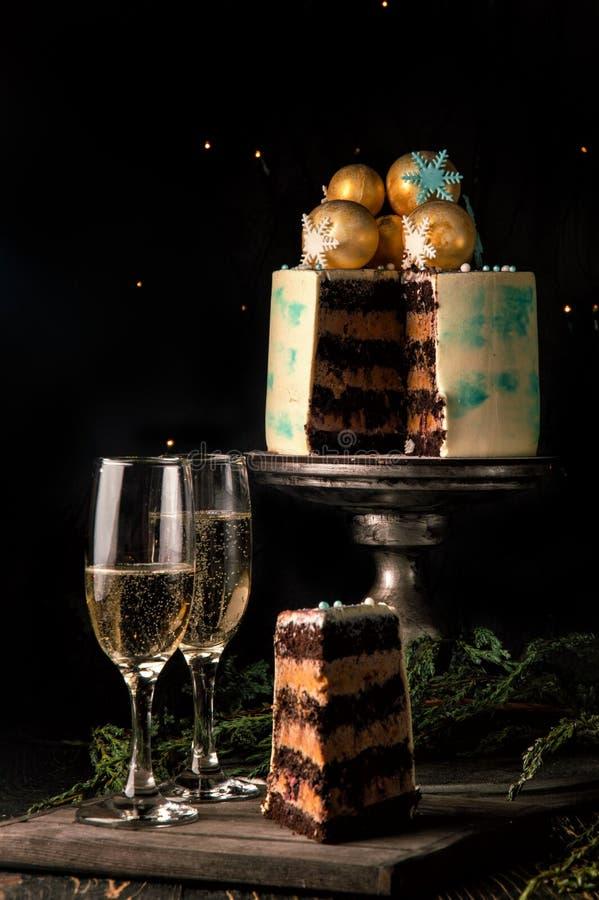 关闭 在裁减的圣诞节蛋糕 附近是有被切的巧克力蛋糕和两块高玻璃片断的一个木板  图库摄影