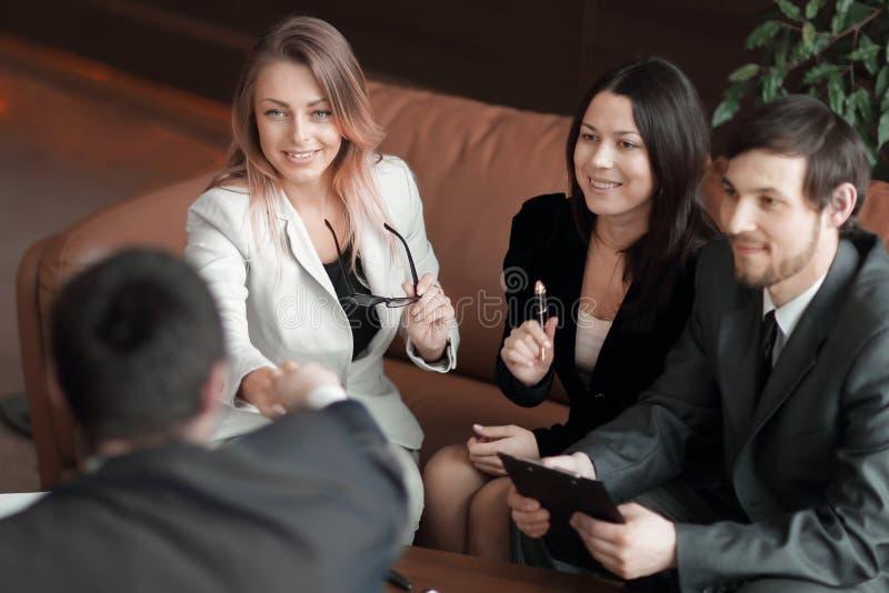 关闭 女商人与坐在工作书桌的商务伙伴握手 免版税库存图片