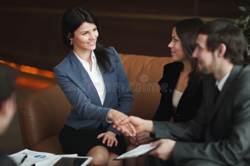关闭 女商人与坐在工作书桌的商务伙伴握手 免版税库存照片