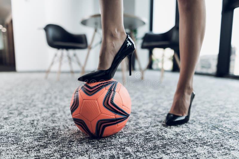关闭 女性脚特写镜头 一条腿在橙色足球站立 在办公室背景 库存图片