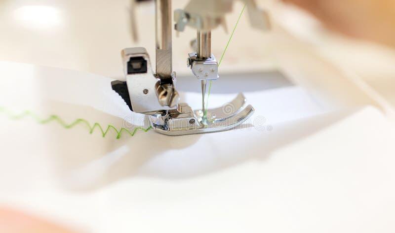 关闭-女性裁缝与缝纫机一起使用 在缝合的期间的职业妇女手与在缝纫机的毛线一起使用 之字形 免版税库存图片