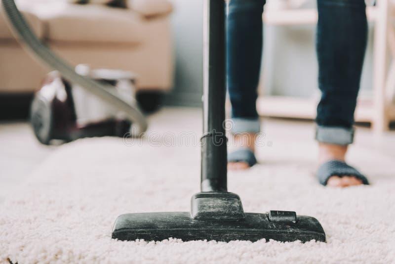 关闭 妇女清洗地毯与吸尘器 免版税库存图片