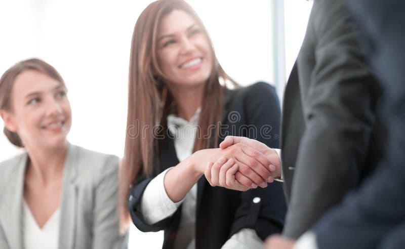 关闭 微笑的女商人与伙伴握手 库存照片