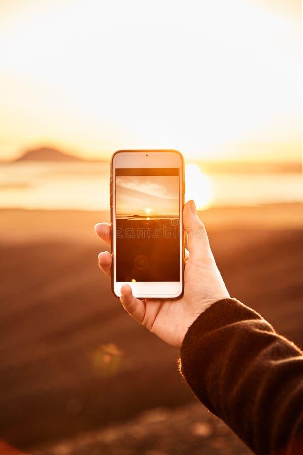 关闭 拍在她的电话的女孩照片 免版税库存照片
