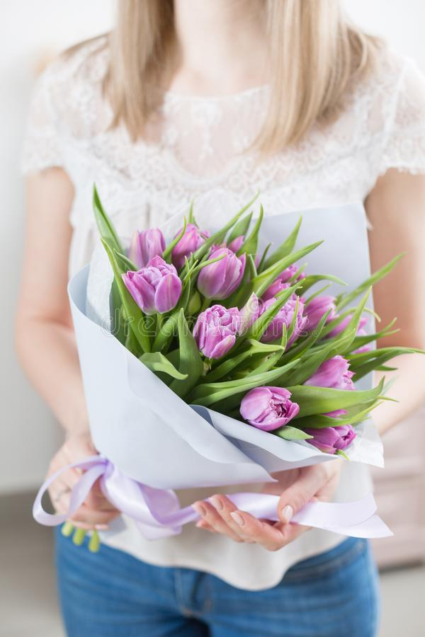 关闭 拿着美好的束紫罗兰色郁金香的年轻愉快的妇女在她的手上 微笑女孩的礼物 花 库存照片