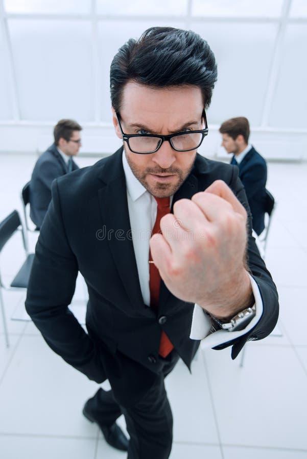 关闭 显示拳头的恼怒的商人 免版税图库摄影